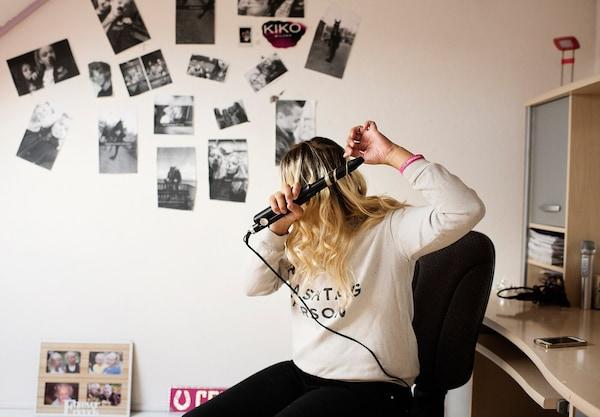 Una donna che arriccia i suoi capelli con un bigodino elettrico - IKEA