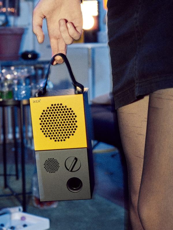 Una donna con collant nere e minigonna che tiene in mano una cassa portatile gialla e nera della collezione FREKVENS - IKEA