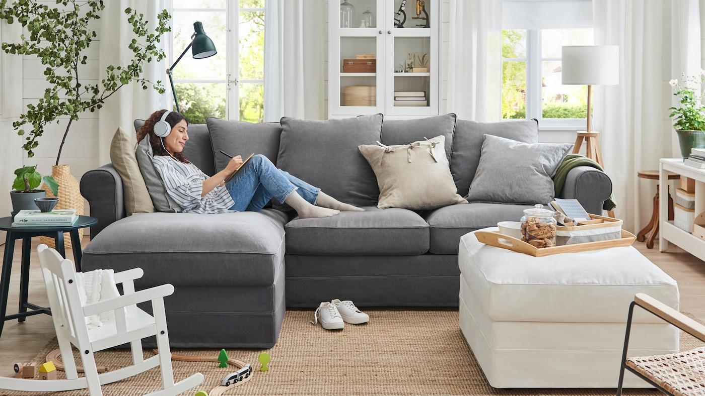 Una donna con le cuffie si rilassa su un divano a tre posti GRÖNLID con chaise-longue in un soggiorno - IKEA