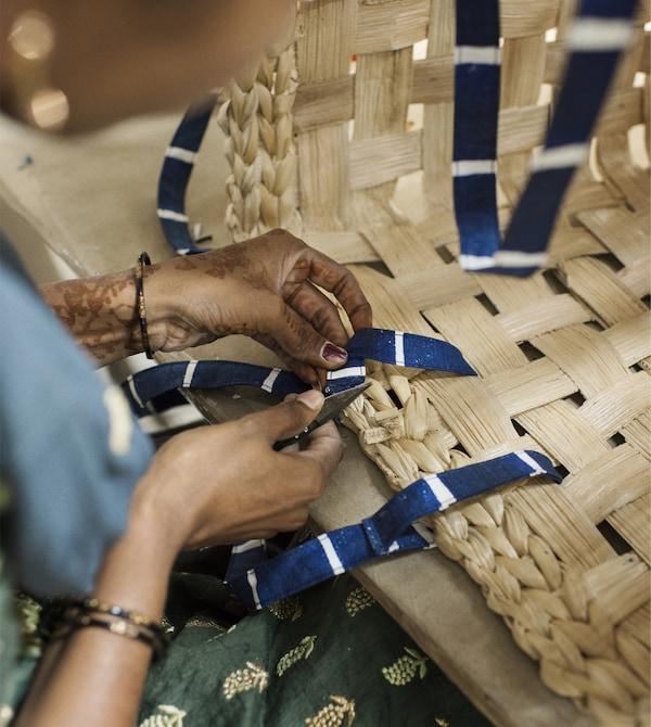 Una donna inserisce delle maniglie di stoffa in una cesta - IKEA