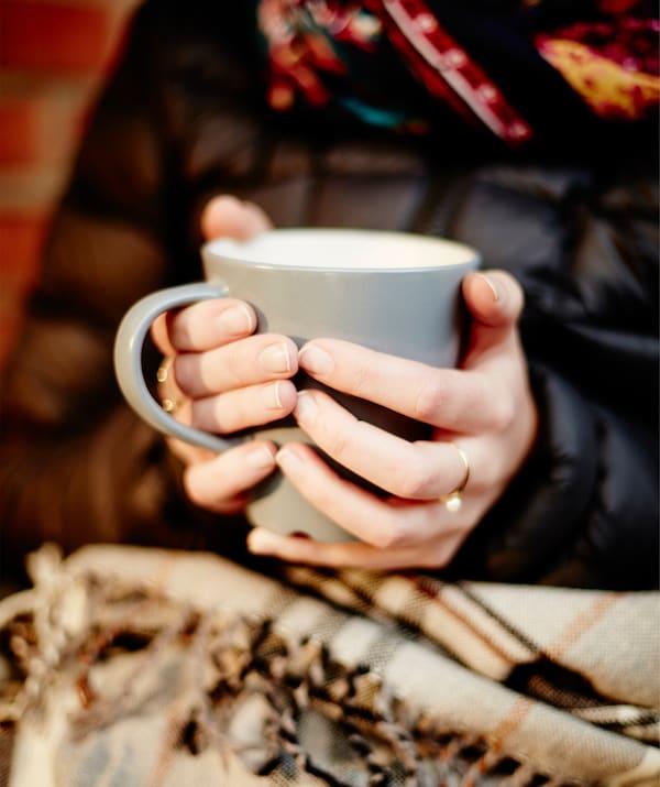 Una donna seduta con abiti pesanti e un plaid sulle gambe regge una tazza fumante con entrambe le mani - IKEA