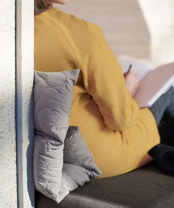 Una donna seduta con un cuscino multiuso grigio OMTÄNKSAM ripiegato tra la schiena e lo schienale della sedia - IKEA