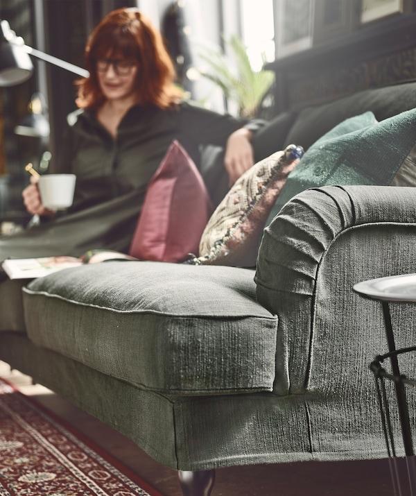 Una donna seduta in una posa rilassata sul divano, accanto a una finestra, regge una tazza e guarda un libro aperto - IKEA