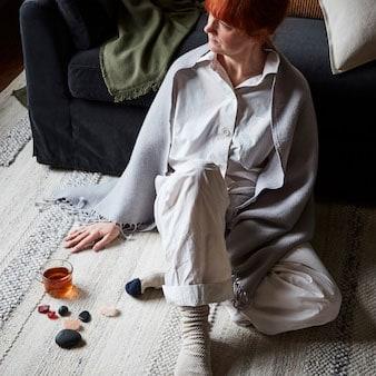 Una donna seduta su un tappeto BRÖNDEN beige fatto a mano, accanto a uno sgabello e un divano FÄRLÖV grigio scuro con cuscini e un plaid - IKEA