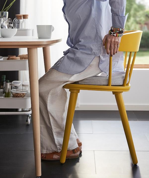 Una donna si siede su una sedia gialla OMTÄNKSAM appoggiandosi allo schienale con le mani - IKEA