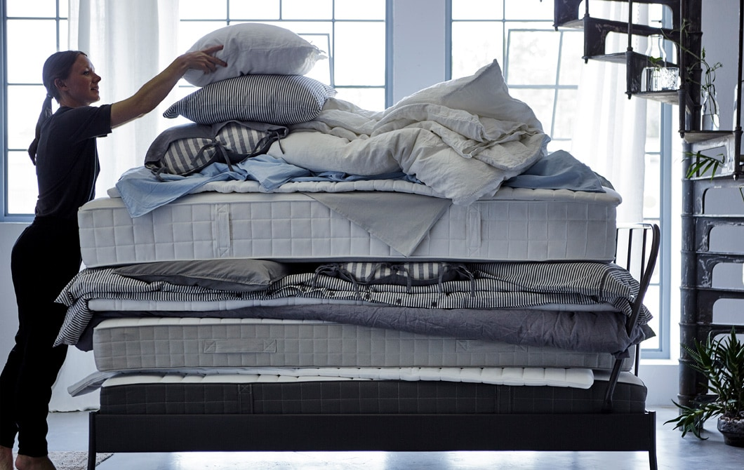 Una donna sistema un cuscino in cima a una catasta di materassi, piumini e biancheria da letto - IKEA