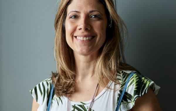Una donna sorridente con i capelli castano chiaro, sullo sfondo una parete grigia - IKEA