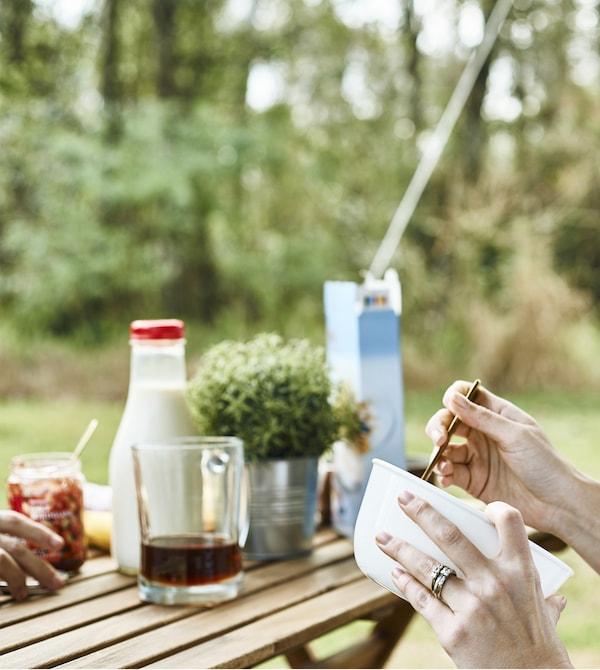 Una donna tiene in mano una ciotola per la colazione su un tavolo all'aperto – IKEA