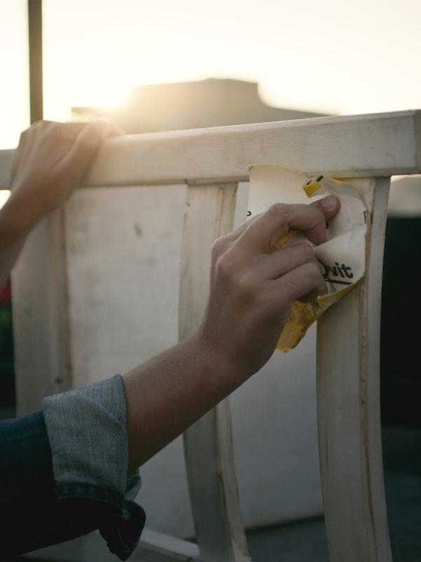 Una donna usa della carta vetrata per scartavetrare una sedia in legno dipinta di bianco, all'aperto con la luce del sole - IKEA