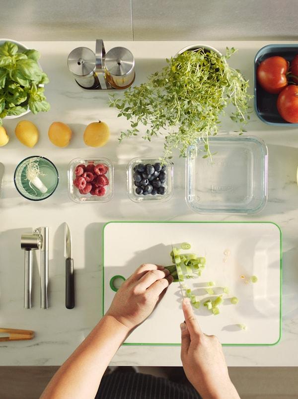 Una encimera blanca en la que hay una persona picando verduras. Hay recipientes de vidrio y porcelana alrededor con frutas y verduras.