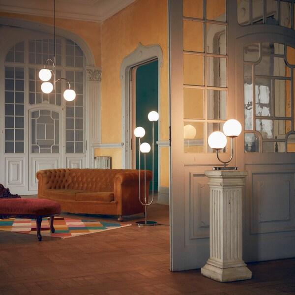 Una estança espaiosa amb tres llums SIMRISHAMN —un de sostre, un de peu i un de taula— amb les cúpules de vidre il·luminades.