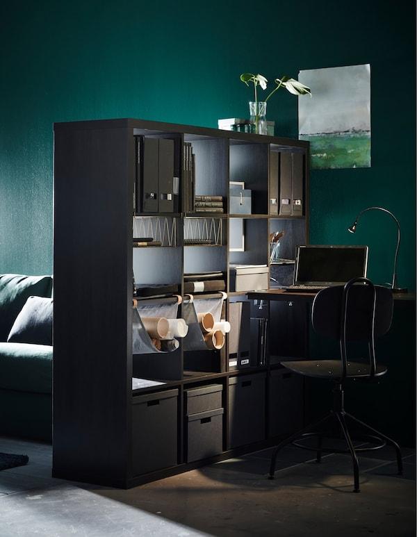Una estantería IKEA KALLAX en negro-marrón que se está utilizando como divisor de espacios para separar una zona de trabajo de la zona de estar.