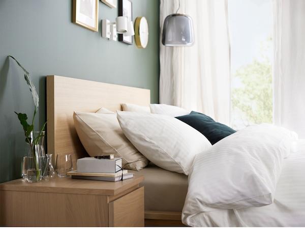 Una estructura de cama y mesita de noche con chapa de roble teñida de blanco y una funda nórdica, fundas de almohadas y cortinas blancas.