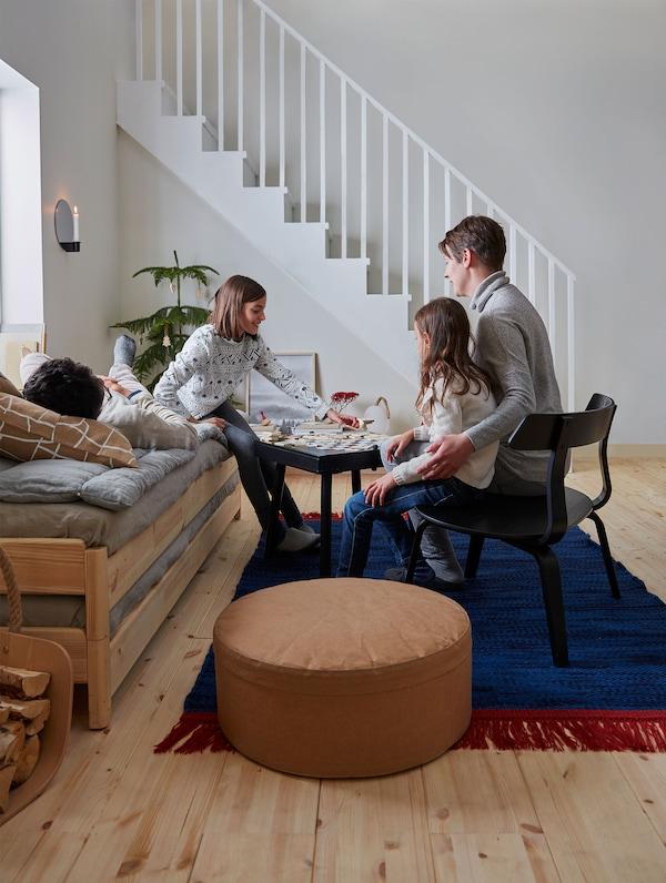 Una familia de cuatro personas se reúne en el salón jugando en la mesa con tablero de ajedrez VÄRMER, sentados en una silla negra y en un diván gris.