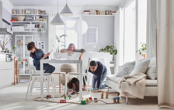 Una familia en su living comedor interactuando. Niños jugando en el suelo, rodeados de mesas y sillas blancas. Lámparas colgando desde el techo blancas con formas de conos y esféras. Sofá estilo futón beige con cojines grises claros.