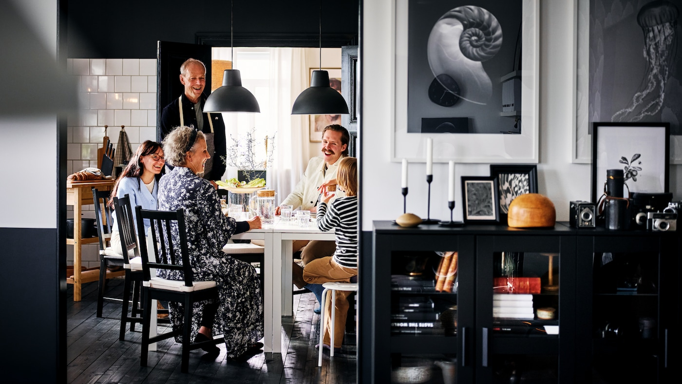 Una familia sonriente sentada en sillas STEFAN en marrón-negro alrededor de dos mesas MELLTORP blancas en un comedor blanco y negro.