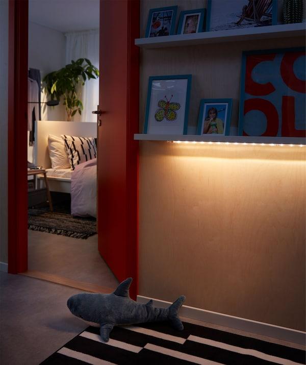 Una fila di luci a LED sotto una mensola per quadri illumina il corridoio, una porta socchiusa fa intravedere una camera da letto - IKEA