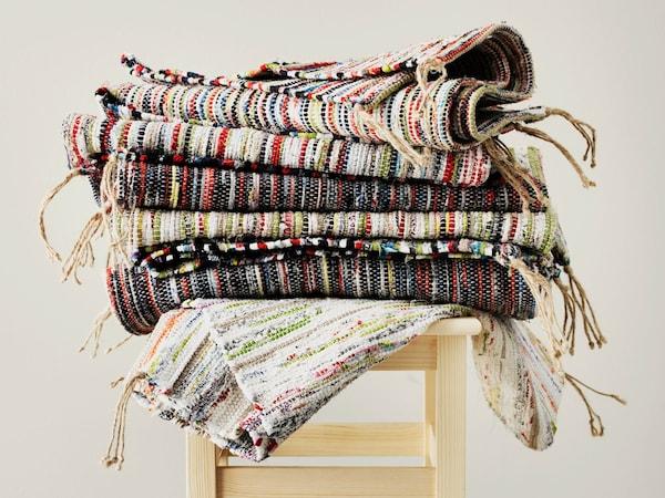 Una foto de coloridas alfombras tejidas de IKEA hechas con retales apiladas unas encima de otras sobre un taburete.