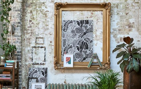Una galleria di tessuti fantasia incorniciati appesi a una parete di mattoni con una grande cornice color oro, piante e una libreria bassa - IKEA