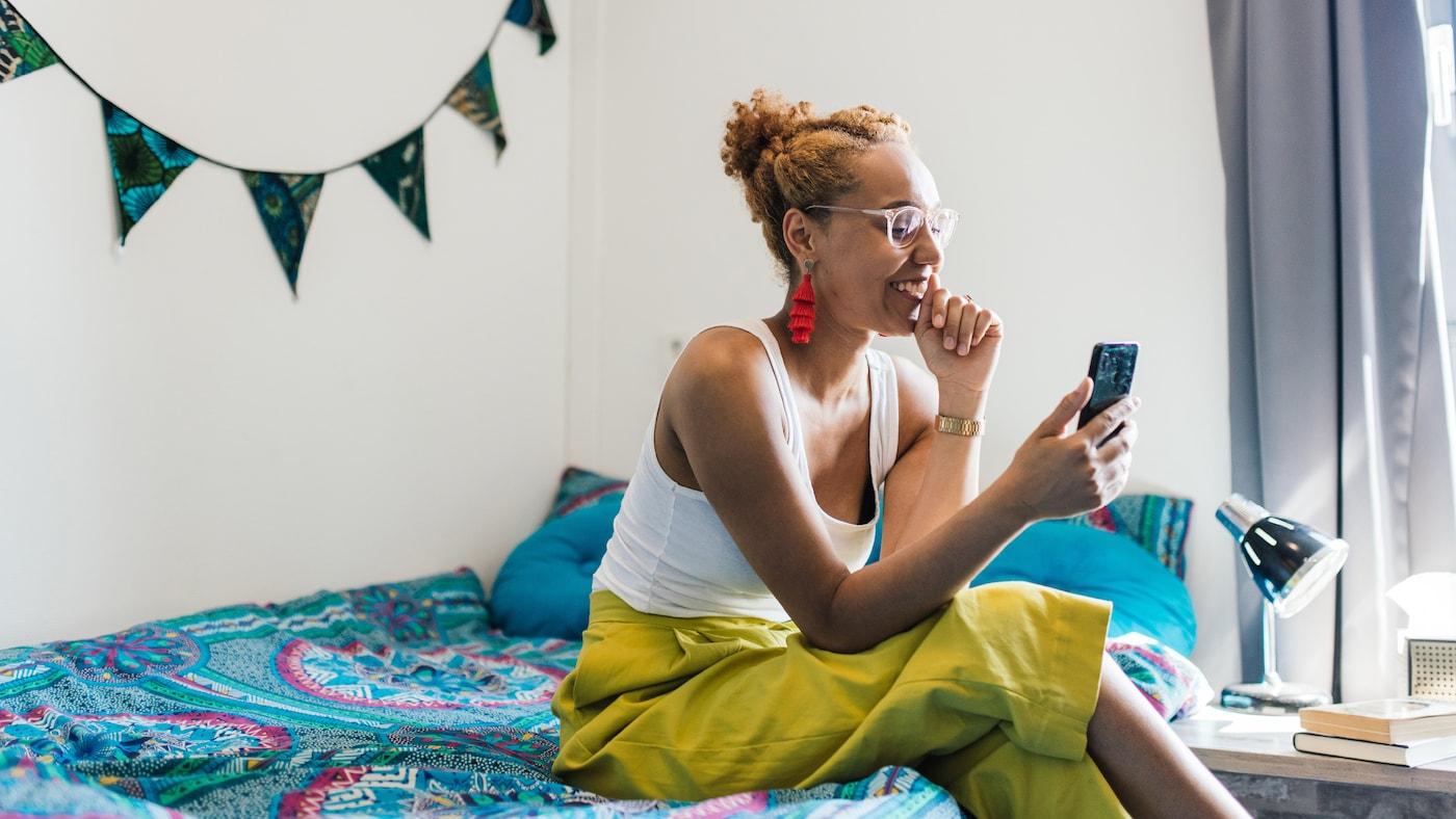 Una giovane donna che indossa pantaloni giallo acceso e un paio di occhiali è seduta sul suo letto. Sta sorridendo al suo telefono.