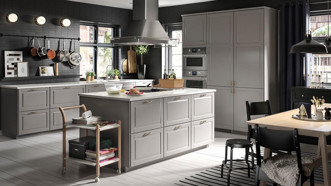 Una grande cucina grigia con un'isola al centro e un tavolo da pranzo in faggio/bianco con sedie e sgabelli neri.