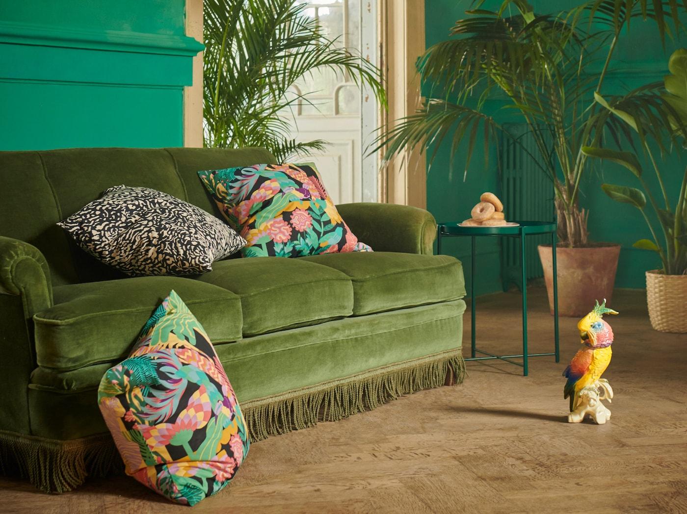 Una grande stanza con varie piante e un divano in velluto verde su cui sono sistemati dei cuscini con fodere GRIMHILD e NÄBBFLY con motivi esotici - IKEA