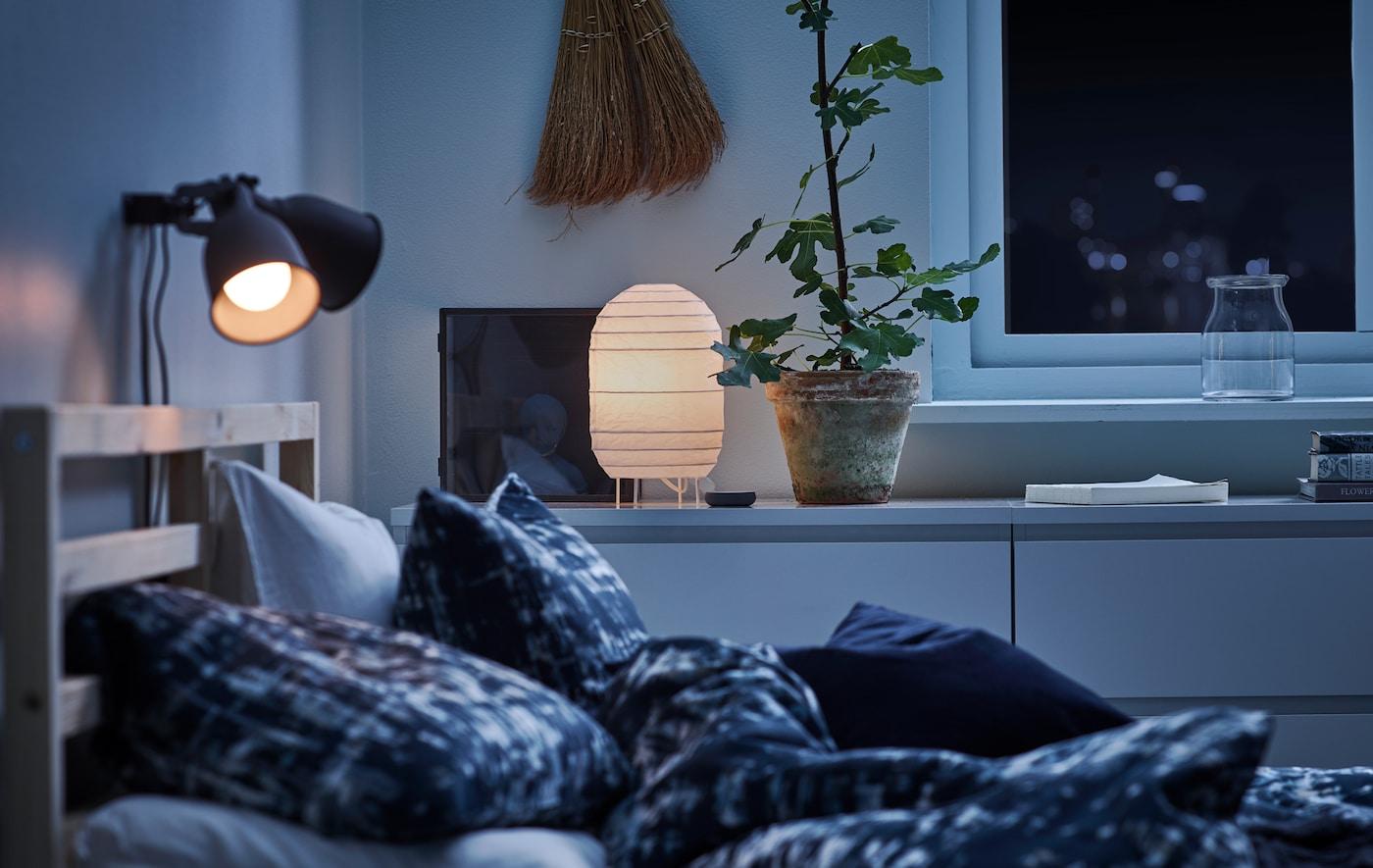 Una habitación a oscuras con ropa de cama de color azul, ligeramente iluminada con una lámpara de papel decorativa y una lámpara de mesa.