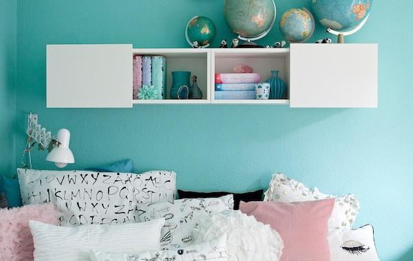Una habitación con paredes en azul pastel y tejidos monocromáticos.