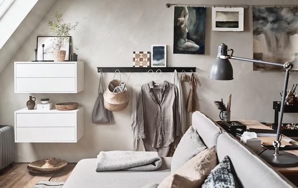 Una habitación con techo abuhardillado con muebles de colores neutros, como por ejemplo un sofá cama y un escritorio.