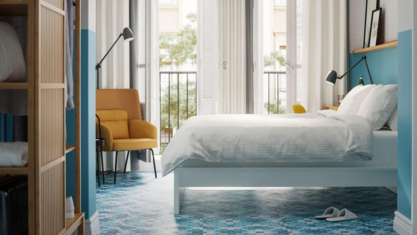 Una habitación con un armario NORDKISA en bambú, una cama blanca con ropa de cama blanca, paredes y suelo azules y un sillón amarillo.