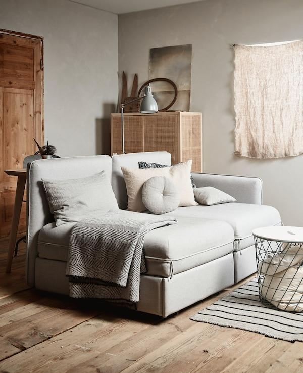 Una habitación con un sofá de color natural, una cesta y un armario en el fondo.