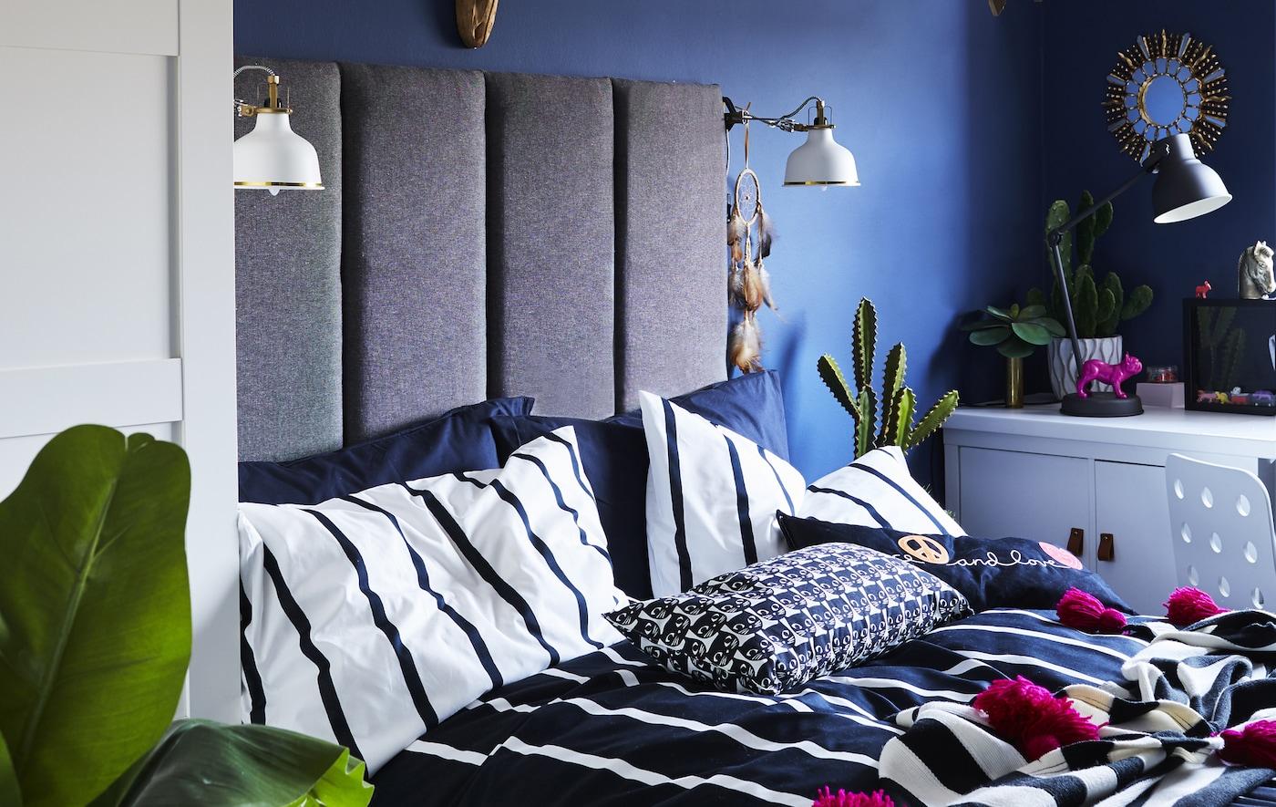 Una habitación infantil con paredes azules, un cabecero gris oscuro montado en la pared con dos lámparas de lectura blancas y ropa de cama de rayas.