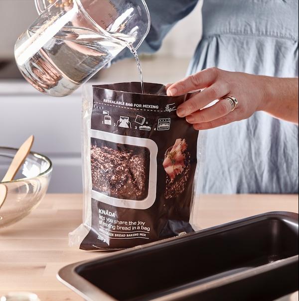 Una jarra vierte agua en un sobre para preparar la mezcla de la masa del pan casero