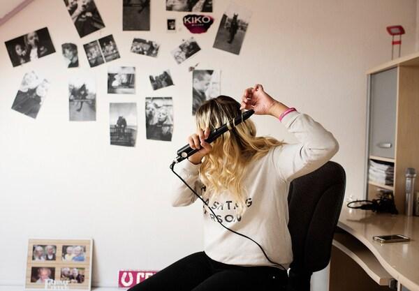 Una joven se riza el pelo con un rizador eléctrico en un cuarto con paredes blancas.