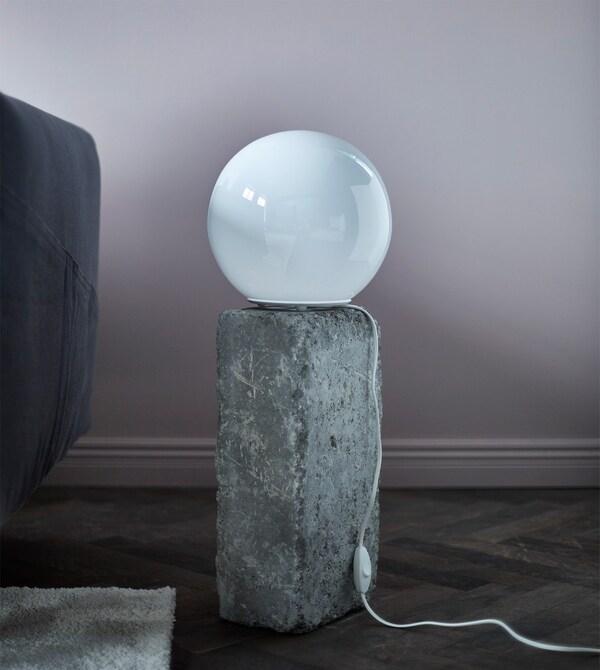 Una lámpara de mesa redonda sobre una roca.