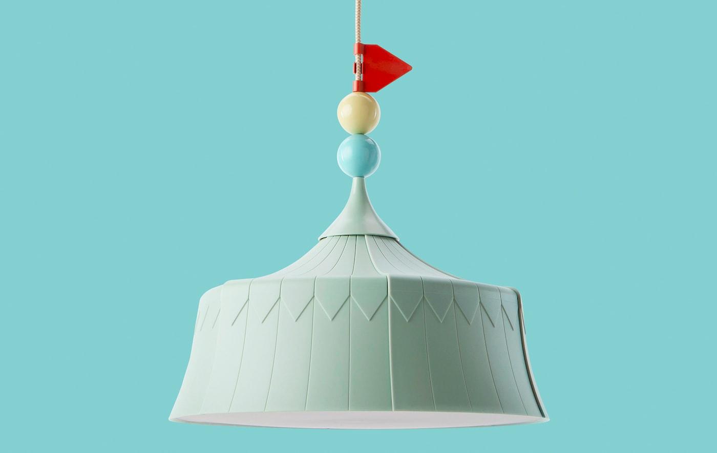 Una lámpara de techo verde con diseño de carpa de circo con fondo de color turquesa.
