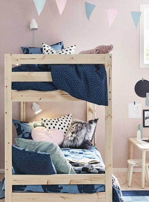 Una litera de madera clara en la habitación de un niño o niña con ropa de cama azul y paredes rosas.
