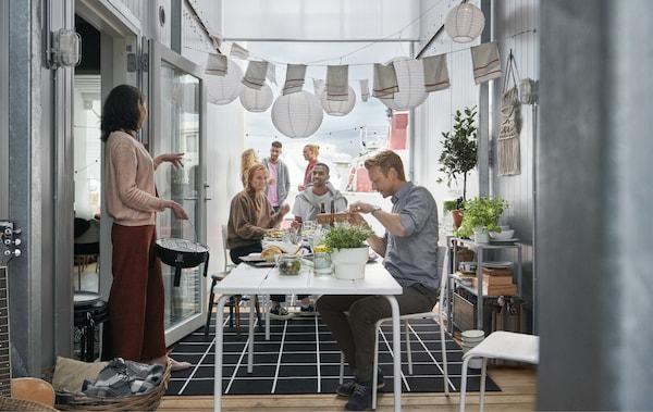 Una lunga tavola apparecchiata in uno spazio tra due container, decorato con lanterne di carta – IKEA