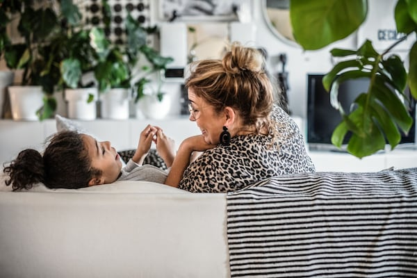 Una madre y su hija sentadas y riendo en un sofa IKEA.