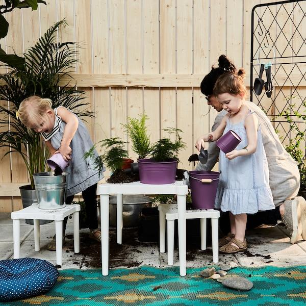 Una mamma e due bambine riempiono i vasi con la terra - IKEA.