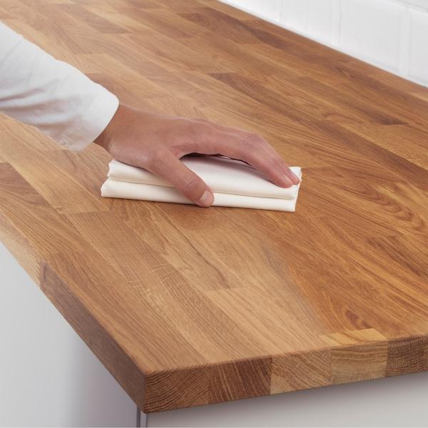 Una mano che strofina un panno bianco sulla superficie di un piano di lavoro in legno.