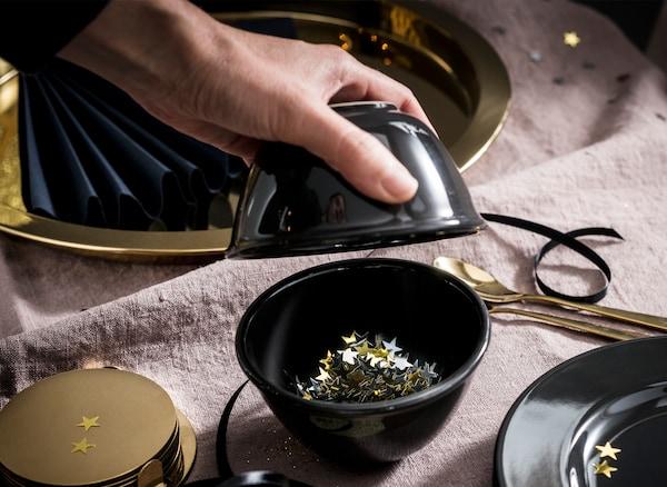 Una mano colocando estrellas doradas en un cuenco negro sobre una mesa decorada con artículos dorados y negros, platos, bandejas y cubertería.