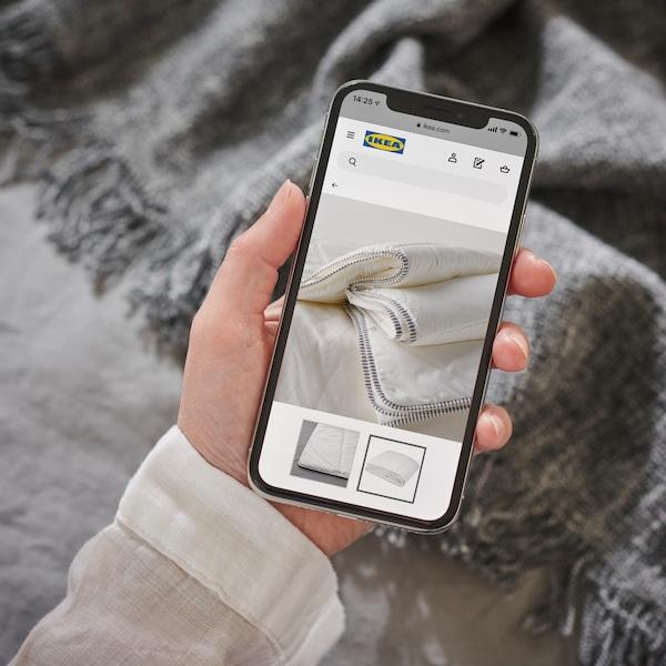 Una mano con un celular navegando en el sitio IKEA online.