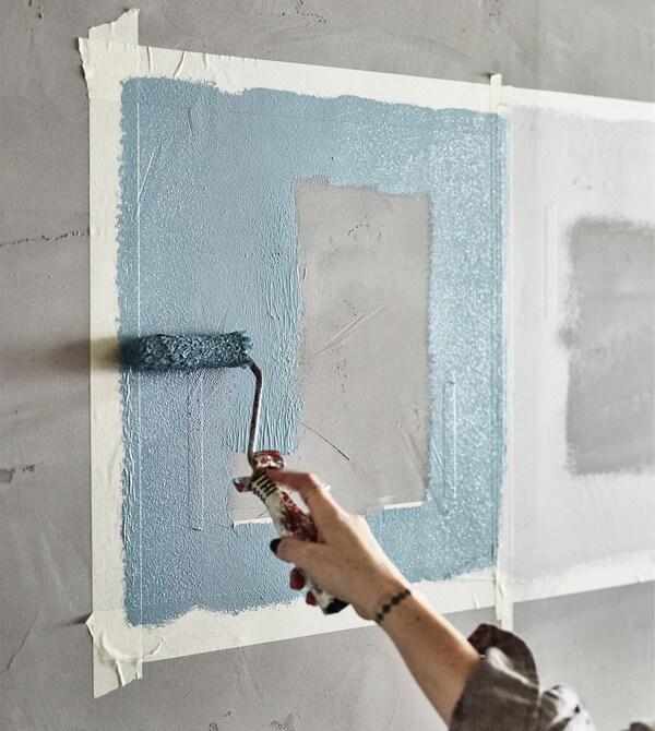Una mano pintando distintos cuadrados de colores en una pared con un rodillo.