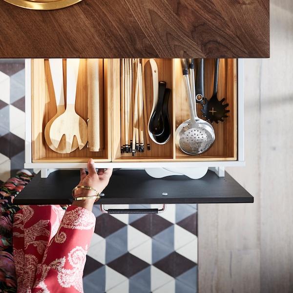 Una mano tirando de un cajón debajo de una encimera de madera oscura con un accesorio de madera lleno de utensilios de cocina.