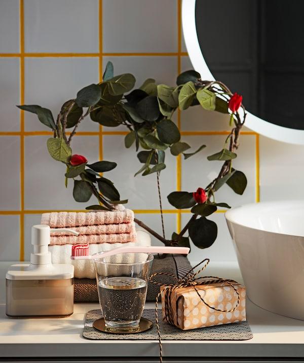 Una mensola del bagno decorata con foglie artificiali di eucalipto SMYCKA di IKEA disposte a forma di cuore