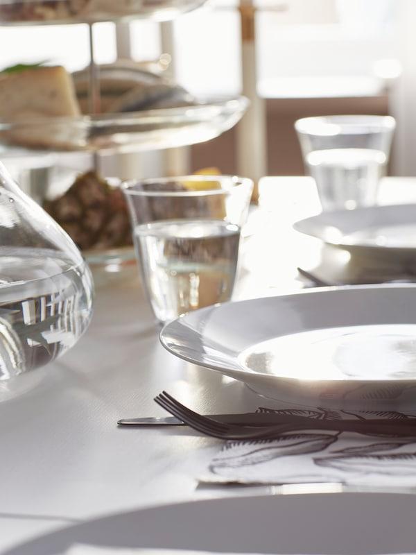 Una mesa con un plato pequeño GLADELIG gris con un cuchillo y un tenedor de acero inoxidable, y un vaso transparente.