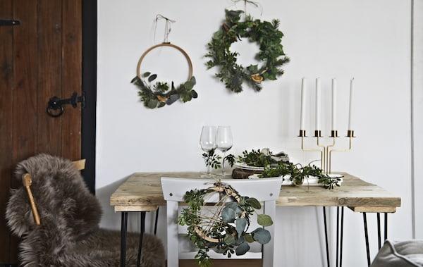 Una mesa decorada con coronas y accesorios navideños.
