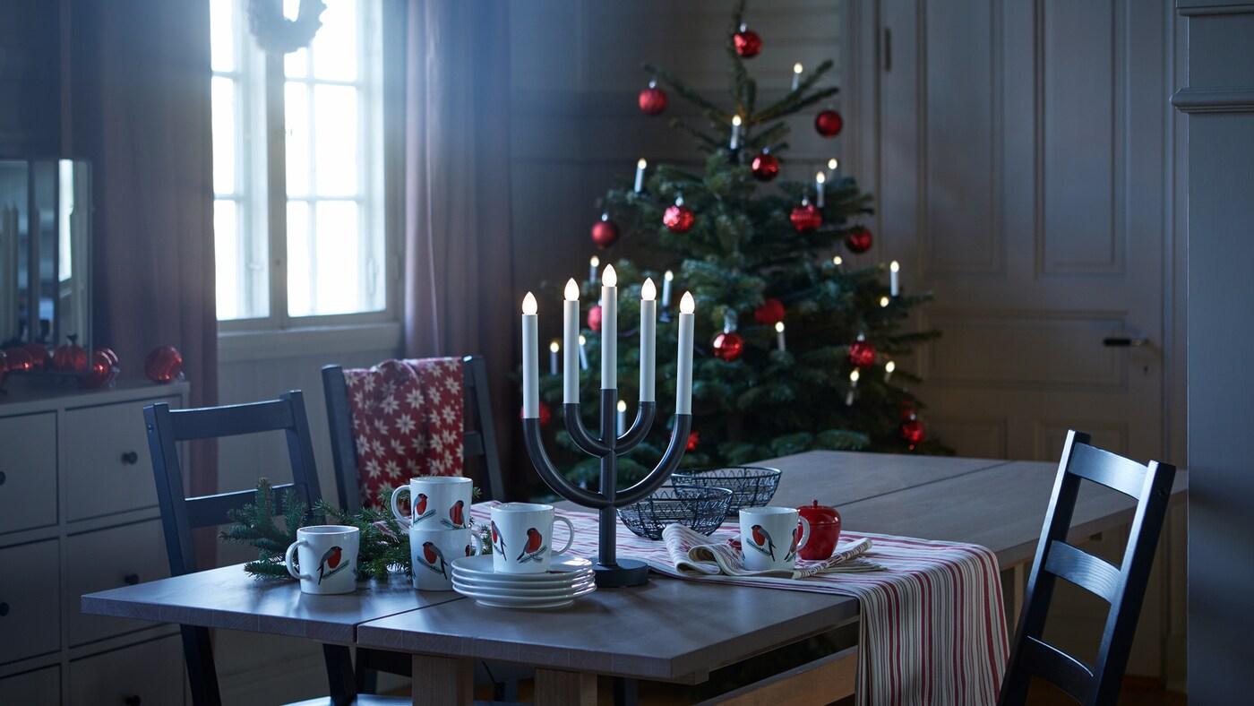 Una mesa extensible KLIMPFJÄLL de color gris-marrón rodeada de varias sillas y preparada para llevar a cabo diversas actividades diarias.