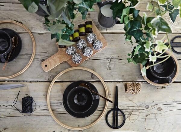 Una mesa llena de herramientas de manualidades, tazas de té y aperitivos.